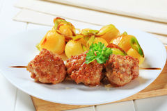 Meatball skewer and potatoes Stock Photos