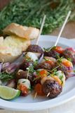 Meatball skewers. Grilled meatball skewers with garlic bread on a plate Royalty Free Stock Photo