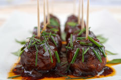 Meatball snacks. With dark barbecue sauce on dish , garnished with chive Stock Image