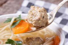 Meatball soup, noodles and carrots in spoon Stock Image