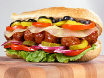 Meatball Sub Sandwich. Meatball submarine sandwich with cheese, lettuce, tomato, onion, red bell pepper, banana peppers, pickles, and black olives Stock Images