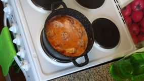 The meatballs in the boiling sauce stand on the stove, the man removes the lid from the pan. The meatballs in the boiling sauce stand on the stove, the man stock video footage