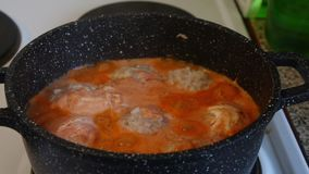 Meatballs in boiling sauce stand on the stove, in a pan with the lid removed. Meatballs in boiling sauce stand on the stove, in a pan with the lid removed stock video footage