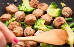 Meatballs, broccoli and spinach stir-fried. Fry meatballs, broccoli and spinach stir-fried in a pan stock image