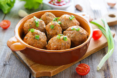 Meatballs in ceramic pan on wooden table stock photography