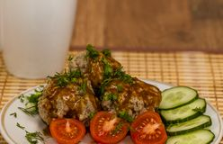 Meatballs covered with sauce. Meatballs with sauce on tha plate with cherry tomatoes and cucumber Stock Photos