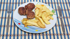 Meatballs with french fries. In a plate Royalty Free Stock Image
