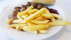 Meatballs garnished with french fries in a white plate Stock Photos