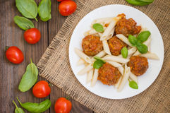 Meatballs with pasta penne in tomato sauce on a white plate. Wooden rustic background. Top view. Close-up Royalty Free Stock Photo