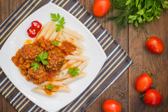 Meatballs with pasta penne in tomato sauce on a white plate. Wooden rustic background. Top view. Close-up Stock Image