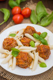 Meatballs with pasta penne in tomato sauce on a white plate. Wooden rustic background. Top view. Close-up Royalty Free Stock Photography