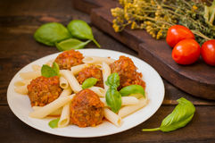 Meatballs with pasta penne in tomato sauce on a white plate. Wooden rustic background. Top view. Close-up Stock Images