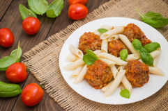 Meatballs with pasta penne in tomato sauce on a white plate. Wooden rustic background. Top view. Close-up Stock Photos