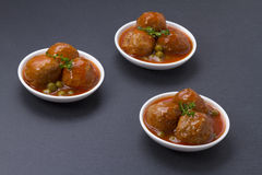 Meatballs with peas and sauce Stock Images