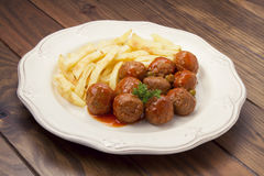 Meatballs with peas, sauce and french fries Stock Photography