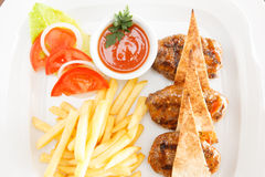 Meatballs in red sauce. Meatballs cooked in tomato sauce with french fries Royalty Free Stock Image