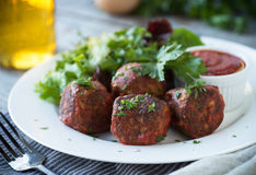 Meatballs and Salad. Delicious meatballs with green salad and tomato sauce stock photo