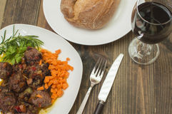 Meatballs in sauce. On the table, glass of wine and bread Stock Photos