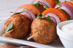 Meatballs on skewers with sauce on a plate macro, horizontal Stock Image