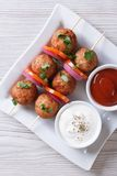 Meatballs on skewers and sauces vertical top view Royalty Free Stock Images