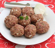 Meatballs. Some raw meatballs with onions and herbs Royalty Free Stock Photos
