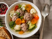 Meatballs soup in white plate on old wooden rustic grey table, top view royalty free stock images