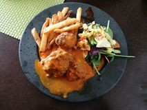 Meatballs with spicy tomato sauce on a plate side with french fries and   spinach feta white cheese and tomato salad on black plat Stock Images