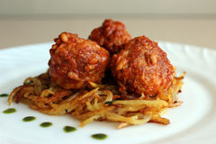 Meatballs in sweet and sour tomato sauce on. A crispy crust of potatoes stock image