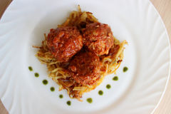 Meatballs in sweet and sour tomato sauce. On a crispy crust of potatoes stock photos