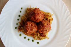 Meatballs in sweet and sour tomato sauce. On a crispy crust of potatoes royalty free stock images