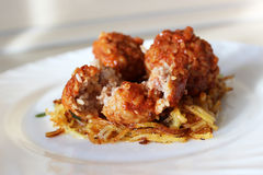 Meatballs in sweet and sour tomato sauce. On a crispy crust of potatoes royalty free stock image