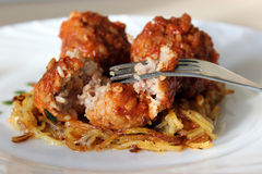 Meatballs in sweet and sour tomato sauce. On a crispy crust of potatoes stock photo