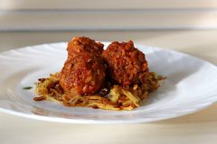 Meatballs in sweet and sour tomato sauce. On a crispy crust of potatoes stock photography