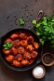 Meatballs in sweet and sour tomato sauce on the kitchen table. stock photos