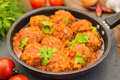 Meatballs in sweet and sour tomato sauce in the pan. Wooden background. Close-up Stock Photography