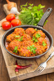 Meatballs in sweet and sour tomato sauce in the pan. Wooden background. Close-up Royalty Free Stock Photography