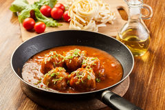 Meatballs with tomato sauce on black pan Stock Images