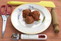Meatballs at the tomato sauce. Dish of meatballs near some utensil kitchen Stock Photos