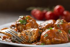 Meatballs with tomato sauce and fresh chopped parsley on plate w Royalty Free Stock Photography