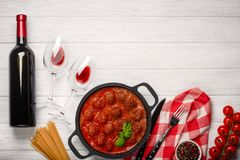 Meatballs in tomato sauce in a frying pan with cherry, tomatoes, bottle of wine and two glasses on a white wooden board stock photo