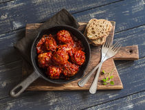 Meatballs in tomato sauce in a pan on rustic wooden cutting board Stock Images
