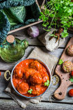 Meatballs with tomato sauce and parsley. On old wooden table stock photo