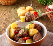 Meatballs with tomato sauce with potatoes in broth. On complex background Royalty Free Stock Images