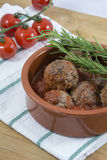 Meatballs with tomato sauce, red cherry and rosemary on the white kitchen towel Stock Photography