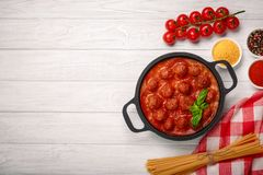 Meatballs in tomato sauce with spices and basil in a frying pan and cherry tomatoes on a white wooden board royalty free stock images