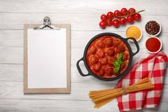 Meatballs in tomato sauce with spices and basil in a frying pan and cherry tomatoes on a white wooden board stock photography