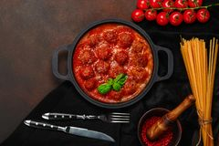 Meatballs in tomato sauce with spices, cherry tomatoes, pasta and basil in a frying pan on rusty brown background stock photo