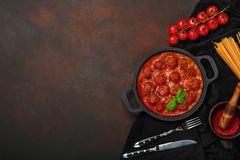Meatballs in tomato sauce with spices, cherry tomatoes, pasta and basil in a frying pan on rusty brown background. Top view royalty free stock image