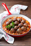 Meatballs with vegetable sauce in cast iron skillet on wooden background royalty free stock photo
