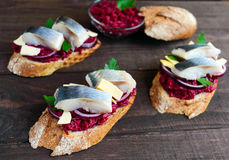 Meatless dietary sandwich: boiled beetroots, purple onion, salted herring and flakes of smoked cheese on a crispy baguette. Royalty Free Stock Images
